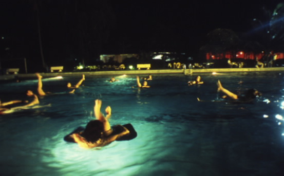 Western expatriates take a break from humanitarian relief operations to practice 'aquatic yoga' at a plush club swimming pool off limits to ordinary Congolese people. Just one of the many perks of relief work in 'exotic' foreign war zones. Photo Keith Harmon Snow, 2007.