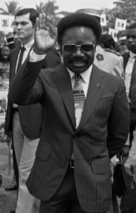 French President Frantois Mitterrand (L) waves to the crowd, 17 January 1983, on his arrival at Leon M'ba airport in Libreville accompanied by his Gabonese counterpart Omar Bongo (R). (Photo credit should read DANIEL JANIN/AFP/Getty Images)