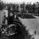 Burial of the dead after the massacre of Wounded Knee. U.S. Soldiers putting Indians in common grave; some corpses are frozen in different positions.