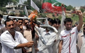 Members of Pakistan Tehreek-e-Insaf (PTI) party burn replica of Drone aircraft near Peshawar Press Club on May 14, 2011. Credit: Ashfaq Yusufzai/IPS