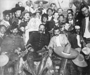 """Villa en la Silla."" Villa in the presidential chair after routing Carranza. Zapata is immediately to his left with the enormous sombrero."