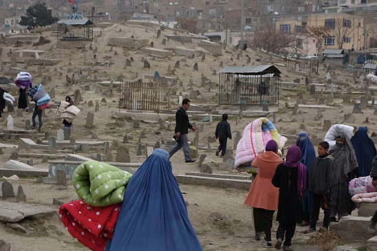 Bearing quilted bed covers, Afghans walk through the cemetery to their mountainside homes.
